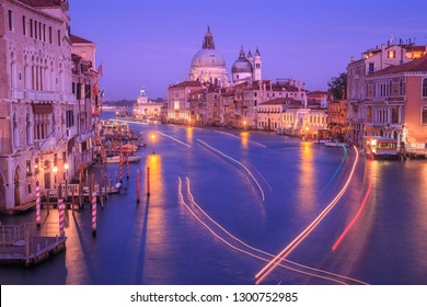 Grand canal with light trails from passing boats and Basilica of Saint Mary of Health (Santa Maria della Salute) in the distance, after sunset, at dusk. View from the Academy bridge in Venice, Italy.