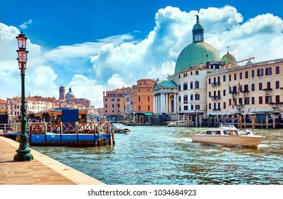 Grand Canal in Venice Italy. Panoramic view to picturesque landscape city and cathedral San Simeone Piccolo. Boat cutter on water. Sunny summery day with blue sky white clouds.