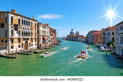 Grand canal in Venice with old houses, boats, the church Santa Maria della Salute in the background and sunburst in the blue sunny sky.