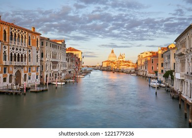 Grand Canal in Venice with Saint Mary of Health basilica, warm light at sunset in Italy