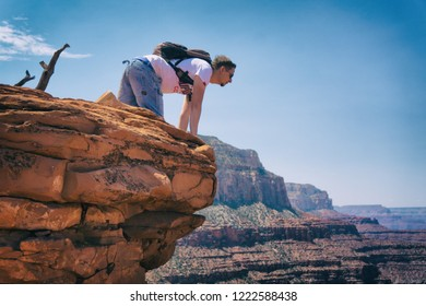 GRAND CANYON, ARIZONA - August 13, 2018: Young man looking over the edge in Grand Canyon, Arizona.