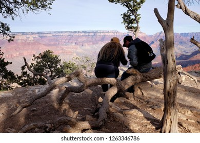 Grand Canyon, Arizona, USA; Nov 2018 - A young couple sits together on a tree branch at the Grand Canyon