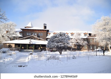 Grand Canyon, AZ., U.S.A. Dec. 31/Jan. 1, 2019.  Grand Canyon National Park's Grand Lady:  El Tovar hotel with a mantle of new snow, falling fine powder snow and the blush of a warm sunrise glow