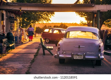 Grand Canyon Caverns and Inn, Route 66, Arizona, USA -  May 14, 2018: Old American classic car Chrysler with sunsetting backlight and woman silhouette in front of grunge motel at famous Route 66, AZ.
