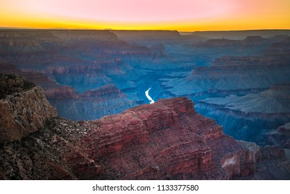 Grand Canyon (Hopi: Ongtupqa) with Colorado River after sunset before dusk. Colorful mountainous landscape background in shades of pink, yellow orange, dark reds and brown to grey blue colors.
