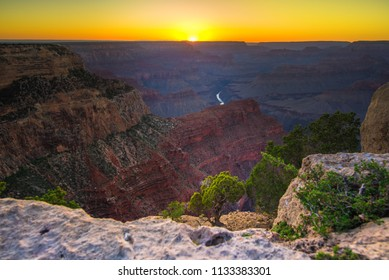 Grand Canyon (Hopi: Ongtupqa) rocky desert with Colorado River and sunset background. South Rim colorful mountainous landscape view in warm color shades of yellow, orange, dark burgundy reds and brown