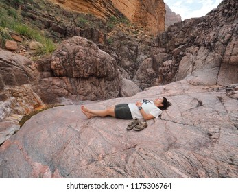 Grand Canyon National Park, Arizona - 05/19/2018: Young woman backpacker rests alongside Monument Creek in Grand canyon National Park, Arizona.