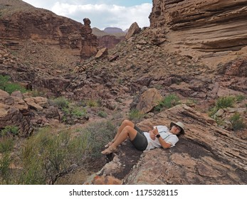 Grand Canyon National Park, Arizona - 05/19/2018: Young woman rests on the rocks at Monument Creek in Grand Canyon National Park, with the monument rock in the background.