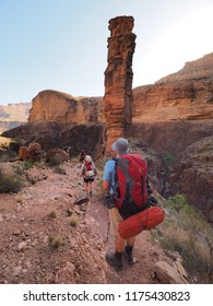 Grand Canyon National Park, Arizona - 05/20/2018: Backpackers hike past the Monument Creek rock formation at sunrise on the Tonto Trail in Grand Canyon National Park.