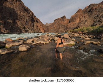Grand Canyon National Park, Arizona - 05/20/2018: Young woman backpacker enjoys some rest at Granite Rapids in Grand Canyon National Park.