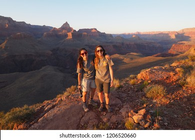 Grand Canyon National Park, Arizona - 05/23/2016: Two young women and sisters enjoy the sunset and view from the northwest tip of Horseshoe Mesa in Grand Canyon National Park, Arizona.