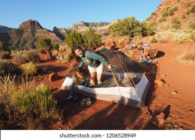 Grand Canyon National Park, Arizona - 05/24/2016: Two young women sleepily exit their tent on Horseshoe Mesa in Grand Canyon national Park, Arizona.