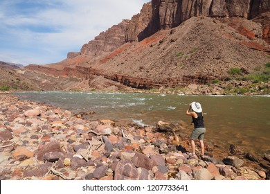 Grand Canyon National Park, Arizona - 05/26/2016: Woman photographs the Granite Gorge from the boulder beach just below Hance Rapids in the Grand Canyon.