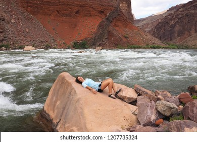 Grand Canyon National Park, Arizona - 05/25/2016: Young woman rests on a boulder at Hance Rapids during a multi-day hike in the Grand Canyon.