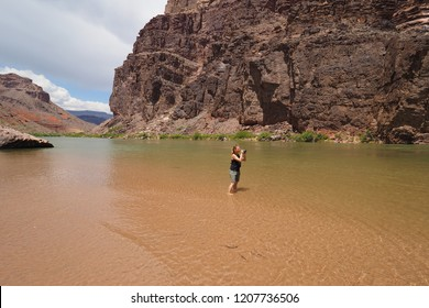 Grand Canyon National Park, Arizona - 05/26/2016: Woman photographs the Granite Gorge from a beach on the Colorado River just above Hance Rapids in the Grand Canyon.