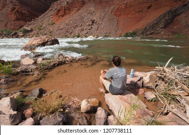 Grand Canyon National Park, Arizona - 05/25/2016: Young woman enjoys the view of Hance Rapids during a multi-day hike in the Grand Canyon.