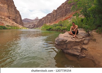 Grand Canyon National Park, Arizona - 05/25/2016: Young man rests on a boulder just above Hance Rapids on the Colorado River during a multi-day hike in the Grand Canyon.