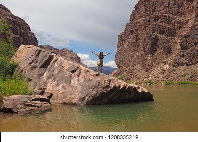 Grand Canyon National Park, Arizona - 05/26/2016: Young woman enjoys expansive view of the inner canyon from a boulder on the Colorado River just above Hance Rapids in the Grand Canyon.