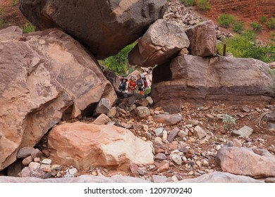 Grand Canyon National Park, Arizona - 05/26/2016: Backpackers seen through a natural window in large boulders on the strenuous New Hance Trail in Grand Canyon National Park.