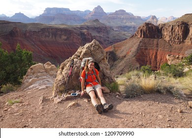 Grand Canyon National Park, Arizona - 05/26/2016: Young female backpacker takes a break during ascent of the very strenuous New Hance Trail in Grand Canyon National Park.