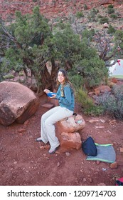 Grand Canyon National Park, Arizona - 05/27/2016: Female backpacker enjoys breakfast on the very strenuous New Hance Trail in Grand Canyon National Park.