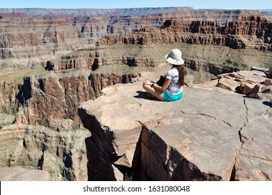 Grand Canyon National Park, West Rim, Arizona, USA. Layered bands of red rock revealing millions of years of geological history. Young white Caucasian woman sitting on the edge facing the canyon.