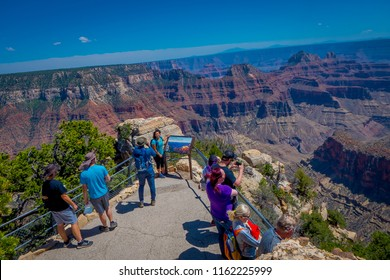 Grand Canyon,Arizona USA, JUNE, 14, 2018: Tourists standing on a steep cliff taking in the amazing view over famous Grand Canyon on a beautiful sunny day in Grand Canyon National Park, Arizona