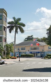 GRAND CAYMAN, CAYMAN ISANDS - CIRCA DECEMBER 2017: Cayman island and territorial flags flying in front of a business