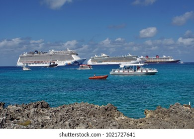 GRAND CAYMAN, CAYMAN ISLANDS - CIRCA DECEMBER 2017: Small boats passing in front of cruise ships moored in the harbor