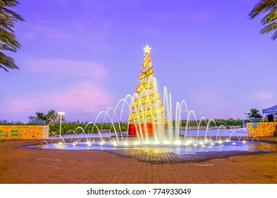 Grand Cayman, Cayman Islands, Dec 2017, Christmas tree in Camana Bay at dusk with a fountain in front of it