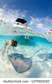 Grand Cayman, Cayman Islands - FEBRUARY 7 2013: Young girl playing with a wild stingray at the Sandbar, Stingray City, Grand Cayman with a boat in the background.