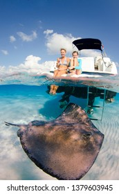 Grand Cayman, Cayman Islands - FEBRUARY 7 2013: Young girl with her mother watching the wild stingrays swim by while they sit on the boat at the Sandbar, Stingray City, Grand Cayman.