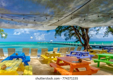 Grand Cayman, Cayman Islands, July 2017, view of the Caribbean Sea from wooden colored tables on the beach at Rum Point
