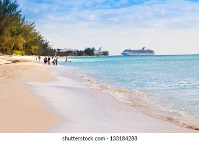 GRAND CAYMAN, CAYMAN ISLANDS - MAR.8:  Tourists enjoying Seven Mile Beach in Grand Cayman on Mar. 8, 2013.  The beach is a local tourist attraction, offering many luxury resorts and water sports.