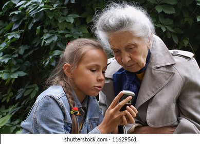 Grand daughter and her grand mother dial mobile phone