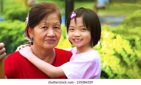 Grand daughter hugging Grandmother in the park.