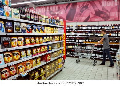 GRAND EST, FRANCE - AUGUST 16, 2017: Customer with shopping cart in the department of alcoholic beverages in a french Super U supermarket.