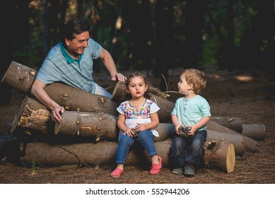 Grand Father looking at his children sitting on log in the dark forest. Horizontal outdoors shot