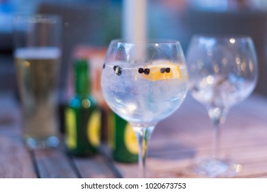 grand gin and tonic with juniper berries and green bottles of tonic in blurred background