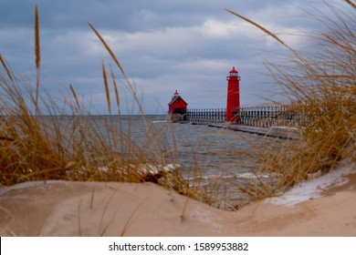 Grand Haven, MI—Dec 15, 2019; ice and snow sits on sand dunes with grass in front of red lighthouse and fog horn building at the entrance to the Grand River shipping channel on Lake Michigan in winter