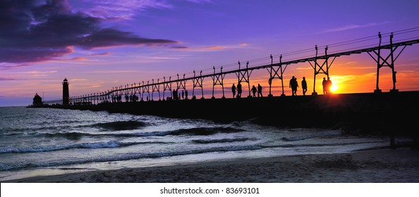 """Grand Haven Lighthouse  """"Sunset silhouette""""  Dozens of people line the Grand Haven Lighthouse pier , watching this beautiful sunset."""