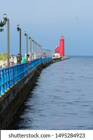 Grand haven, MI 7/23/17- Fisherman on the boardwalk in Grand Haven Michigan near the iconic red lighthouse without the catwalk.