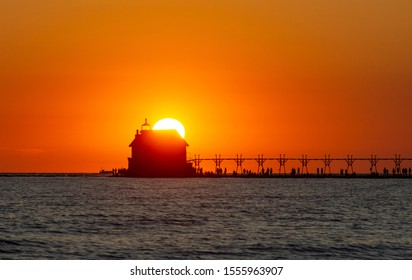 The Grand Haven, Michigan, pier, catwalk and lighthouse shown in silhouette against a bright orange sky and the setting sun