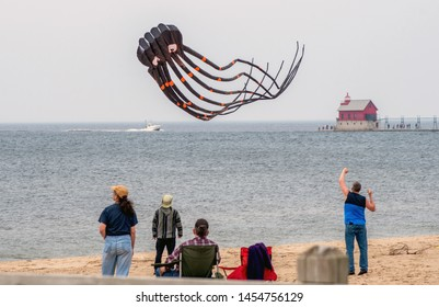Grand Haven Michigan ,USA, May 17, 2019; people watch a flying octopus soaring through the sky by the Grand Haven lighthouse, and during the Grand Haven kite festival event.