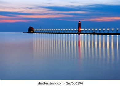 Grand Haven Pier at Night - Lights twinkle like stars.The catwalk runs between the inner and outer lighthouses. Patterns reflect on Lake Michigan.