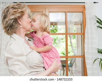 Grand mother carrying infant grand daughter in her arms, hugging and kissing on the lips, showing love and affection at home.