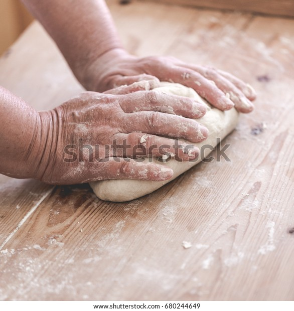 Grand mother makes traditional dumplings. Close up on working hands. Saturated faded tones