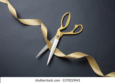 Grand opening. Gold scissors cutting gold silk ribbon, black background, top view, copy space