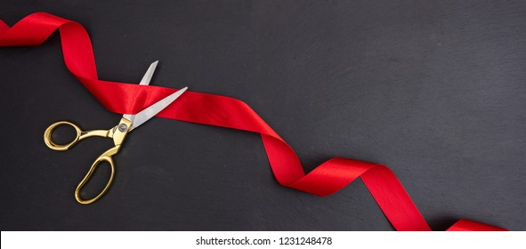Grand opening invitation card template. Gold scissors cutting red silk ribbon against black background, Top view, banner, copy space.
