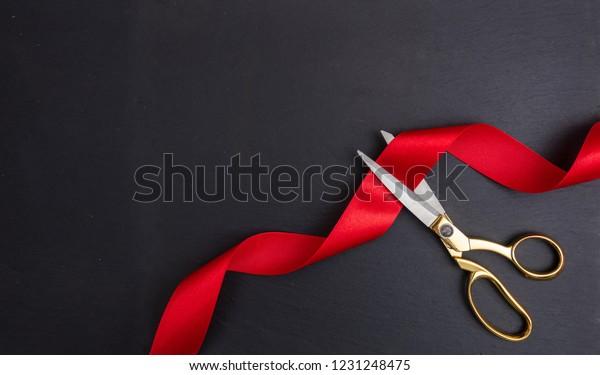 Großartige Eröffnung. Draufsicht der goldenen Schere, die rotes Seidenband auf schwarzem Hintergrund schneidet, Kopienraum